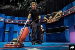 A stagehand vacuums the carpet as preparations continue Oct. 17, 2016, at the University of Nevada, Las Vegas for the final debate Wednesday between Democratic presidential nominee Hillary Clinton and Republican presidential nominee Donald Trump.