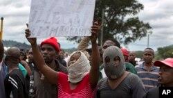 Des Sud-Africains brandissent des pancartes anti-immigration lors d'une manifestation à Pretoria, Afrique du Sud, 24 février 2017.