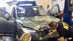In this March 20, 2018, photo provided by the National Transportation Safety Board, investigators examine a driverless Uber SUV that fatally struck a woman in Tempe, Ariz. (National Transportation Safety Board via AP)
