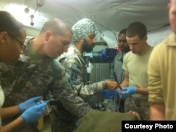 Major Kamal Kalsi works on a patient at Camp Dwyer in Helmand province, Afghanistan, 2011. (Photo courtesy of Major Kalsi)