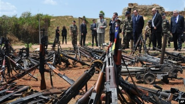 French President Francois Hollande, third right, and his Defense Minister Jean-Yves Le Drian, second right, inspect arms confiscated from ex-Seleka rebels and Anti-balaka militia by the French military of operation Sangaris, and displayed at a French mili