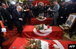FILE - Tunisian President Beji Caid Essebsi decorates members from the presidential guards who were killed in a bomb blast on a bus in central Tunis the previous day during a ceremony at Carthage Palace, Tunis, Nov. 25, 2015.
