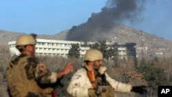 Afghan security personnel stand guard as black smoke rises from the Intercontinental Hotel, Jan. 21, 2018, after an attack in Kabul, Afghanistan.