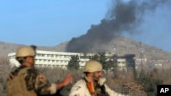 Afghan security personnel stand guard as black smoke rises from the Intercontinental Hotel, Jan. 21, 2018, after an attack in Kabul, Afghanistan. Gunmen stormed the hotel and set off a 12-hour gun battle with security forces that continued into Sunday morning, as frantic guests tried to escape from fourth- and fifth-floor windows.