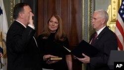 Wakil Presiden AS Mike Pence (kanan) mengambil sumpah Direktur CIA Mike Pompeo (kiri), yang didampingi istrinya Susan, di Gedung Putih (23/1). (AP/Susan Walsh)
