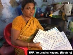 Maragatham Poomari holds her daughter's school certificates in their home in Ayanapuram village in Tamil Nadu, India, July 27, 2017.