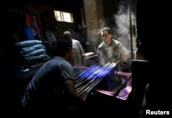 Mohamed Mostafa, 35, and Hisham Aly, 37, work at a dye workshop in old Cairo, Egypt, March 17, 2016.