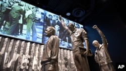 A statue of the 1968 Olympics Black Power salute is on display at the National Museum of African American History and Culture in Washington, Sept. 14, 2016.