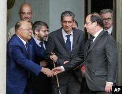 "FILE - French President Francois Hollande shakes hands with Paris Mosque rector Dalil Boubakeur, left, after a meeting with religious representatives in Paris, July 27, 2016. Hollande said the excesses of U.S. presidential candidate Donald Trump ""make you want to retch."""