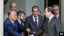 فرانسوا هولاند، رئیس جمهور فرانسه، حین دست پرسی با دلیل بوباکر، امام مسجد جامع پاریس
