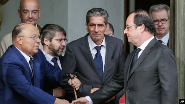 French President Francois Hollande shakes hands with Paris Mosque rector Dalil Boubakeur, left, after a meeting with religious representatives at the Elysee Palace in Paris, following yesterday attack at a church in Normandy, July 27, 2016.