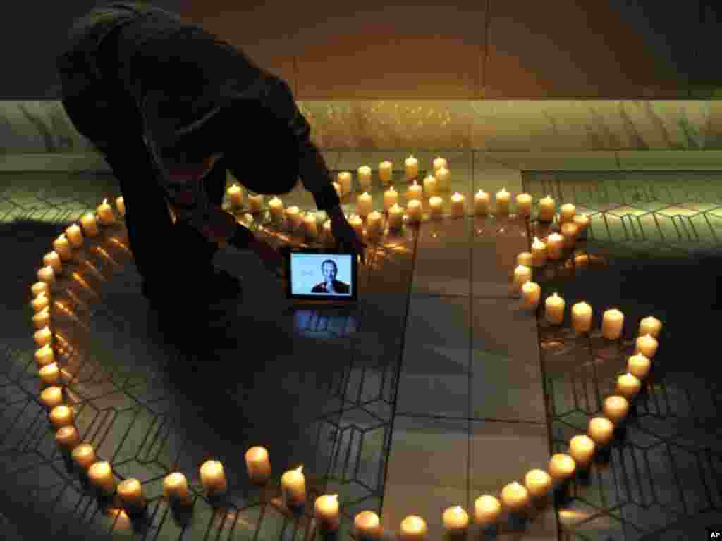 A man places an iPad displaying a picture of Steve Jobs around candles forming the logo of Apple Inc., the company he co-founded, in Chengdu in southwestern China's Sichuan province, on Thursday, Oct. 6, 2011.