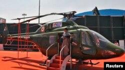 Seorang perempuan berpose di depan helikopter milik Angkatan Udara India (IAF) di bandara militer Yelahanka, Bengaluru (Foto: dok).