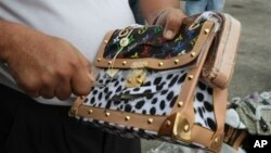 Government worker slashes counterfeit Louis Vuitton handbag during ceremonial destruction of fakes goods seized in raids, Manila, Philippines, June 30, 2011.