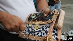 在菲律宾马尼拉政府工作人员在处理打击假冒产品行动中缴获的商品,割开假冒的路易威登皮包