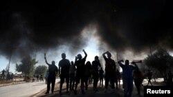 Masyarakat dari kelompok kurang mampu meneriakkan slogan-slogan memprotes minimnya bantuan dari pemerintah dalam masa karantina wilayah di tengah wabah virus corona (Covid-19) di Santiago, Chili, 25 Mei 2020. (Foto: Reuters)