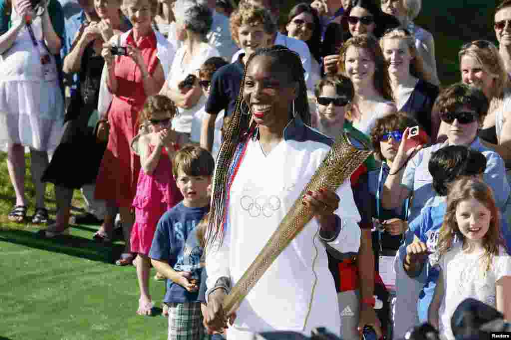 Venus Williams of the U.S. waits with the Olympic Torch on Murray Mound (also known as Henman Hill) at the All England Lawn Tennis Club before the start of the London 2012 Olympic Games in London July 23, 2012.