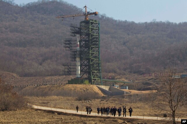 FILE - A group of journalists walk down a road in front of North Korea's Unha-3 rocket at the Sohae Satellite Station in Tongchang-ri, North Korea, April 8, 2012.