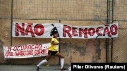 Um jogador de futebol chuta uma bola durante o torneio organizado pela Copa Popular, com participação de 10 favelas, para protestar contra remoções forçadas. 15 de Junho de 2013.