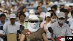 Dân chúng đeo khẩu trang khi đi trên xe máy tại Hà Nội