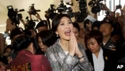 Mantan Perdana Menteri Thailand Yingluck Shinawatra (tengah) meninggalkan parlemen di Bangkok (22/1). (AP/Sakchai Lalit)