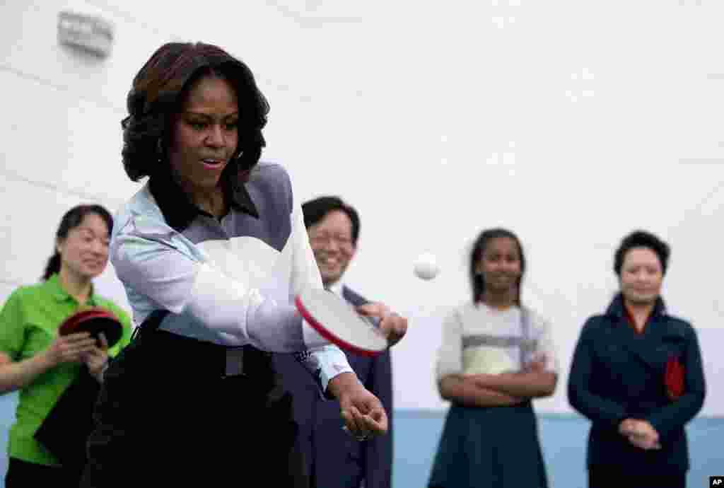 Đệ nhất phu nhân Mỹ Michelle Obama chơi bóng bàn trong khi bà Bành Lệ Viện, phu nhân của Chủ tịch Trung Quốc Tập Cận Bình, và những người khác đứng nhìn trong chuyến thăm của họ đến một ngôi trường ở Bắc Kinh giúp chuẩn bị cho học sinh theo học đại học nước ngoài ở Bắc Kinh, Trung Quốc.