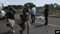 Un migrant tombé d'un véhicule est décédé alors que d'autres migrants marchent dans la banlieue de Tapachula, au Mexique, le 22 octobre 2018.