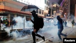 Manifestantes prodemocracia en Hong Kong huyen de gases lacrimógenos lanzados por la policía durante una marcha el Día de Año Nuevo el 1 de enero de 2020.