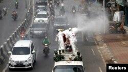 Para petugas Palang Merah Indonesia mengenakan baju hazmat menyemprotkan disinfektan untuk mencegah penularan virus corona (COVID-19), Jakarta, 28 Maret 2020. (Foto: Reuters)