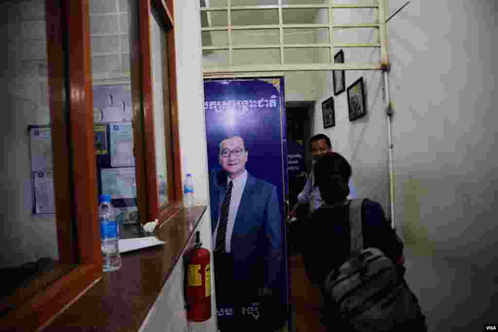 A portrait of former CNRP's President Sam Rainsy is displayed at the main gate of the party's headquarters as VOA journalists pass by during the election night of June 2, 2017. Mr. Rainsy once announced that the June 4 commune elections results could lead his return from exile. (Aun Chhengpor/VOA Khmer)