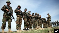 FILE - Afghan National Army soldiers stand in formation following weeks of heavy clashes with Taliban fighters in Dahna-e-Ghori district, Baghlan province, Afghanistan, Mar. 15, 2016.
