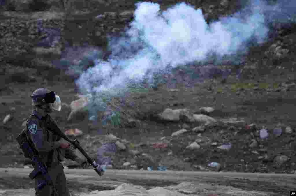 An Israeli border policeman fires a tear gas canister during clashes with Palestinian protesters, outside the Ofer military prison, near the West Bank city of Ramallah.