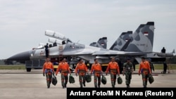 FILE - Indonesian Air Force Sukhoi fighter pilots and crew walk across the tarmac at the Hang Nadim Airport after training for an upcoming military exercise, Oct. 3, 2016.