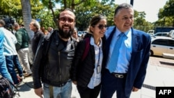 El fotógrafo colombiano Leonardo Muñoz (I) y la periodista colombiana Mauren Barriga Vargas (C) aparecen en la foto junto al encargado de negocios de Colombia en Venezuela, Germán Castaneda, luego de ser liberado de la detención por las autoridades venezolanas, en Caracas.