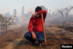 A volunteer takes a break from battling wildfires in Portezuelo, Chile, Jan. 30, 2017.