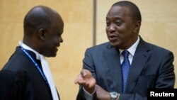 Kenya's President Uhuru Kenyatta (R) speaks to a member of his defense team as he appears before the International Criminal Court at The Hague, Oct. 8, 2014.