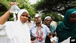 Abdirahman Kwaral (C), a Somali journalist working for a local TV station is tended to as he is admitted into a local hospital after he was injured in a suicide bomb explosion in Mogadishu, 03 Dec 2009