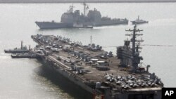FILE - U.S. aircraft carrier USS Ronald Reagan anchors as U.S. Aegis Ship passes after they arrive at Busan port for joint military exercises in Busan, South Korea. The United States and South Korea started joint naval exercises, Nov. 11, 2017, that will involve three U.S. aircraft carriers in what military officials describe as a clear warning to North Korea.
