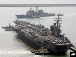 U.S. aircraft carrier USS Ronald Reagan anchors as U.S. Aegis Ship passes after they arrive at Busan port for joint military exercises in Busan, South Korea. The United States and South Korea started joint naval exercises, Nov. 11, 2017.