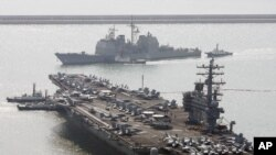 FILE - U.S. aircraft carrier USS Ronald Reagan anchors as U.S. Aegis Ship passes after they arrive at Busan port for joint military exercises in Busan, South Korea.