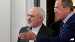 Menteri Luar Negeri Rusia Sergey Lavrov (kanan) menyambut mitranya dari Iran, Mohammad Javad Zarif, di Moskow (17/8). (AP/Ivan Sekretarev)