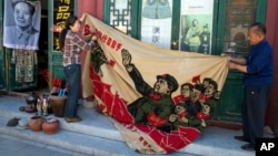 """北京旧货市场上的1969年的文革横幅画布,上面有戴红卫兵袖章的毛泽东、其他文革领导人和红卫兵。横幅上写着""""大海航行靠舵手"""" 和""""毛主席检阅文化革命大军""""(2016年5月16日)"""