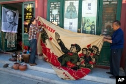 """北京旧货市场上的1969年的文革横幅画布,上面有戴红卫兵袖章的毛泽东、江青和红卫兵。横幅上写着""""大海航行靠舵手"""" 和""""毛主席检阅文化革命大军""""(2016年5月16日)"""