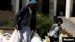 A man carries sacks of wheat flour he received from a local charity during the holy month of Ramadan in Sanaa, Yemen, May 29, 2017.