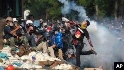 Người biểu tình ném lựu đạn cay trở lại cảnh sát gần tòa nhà chính phủ ở Bangkok, ngày 2/12/2013.