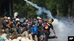Seorang demonstran anti-pemerintah melemparkan kembali gas air mata yang ditembakkan oleh polisi anti huru-hara di Bangkok (2/12). (AP/Wason Wanichakom)
