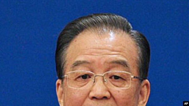Chinese Premier Wen Jiabao gestures as he answers questions during a press conference after the closing session of the annual National People's Congress in Beijing's Great Hall of the People Monday, March 14, 2011.