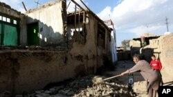 Warga Afghanistan membersihkan reruntuhan bangunan pasca gempa di ibukota Kabul, Senin (26/10).