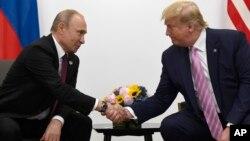 2019年6月28日特朗普(右)在日本大阪舉行的20國集團峰會期間與俄羅斯總統普京握手。