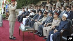 In this image released by the Egyptian President, an Egyptian military officer salutes President Mohammed Morsi, third from right at a graduation ceremony at a military base east of Cairo, Egypt, July 9, 2012.